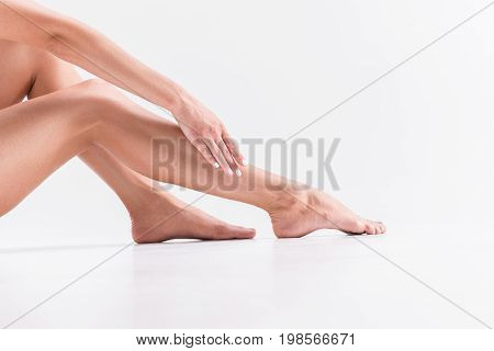 Close up of barefoot legs of young lady. She is sitting on floor and touching them by hand. Smooth skin concept