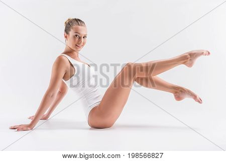 Full length portrait of happy youthful sport woman sitting on floor, leaning backward on hands. She is smiling and raising legs with stretched toes and bent knees
