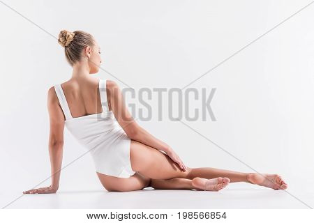 Pensive young woman gymnast is sitting gracefully on floor. She is relaxing and looking to distance. Focus on back. Copy space