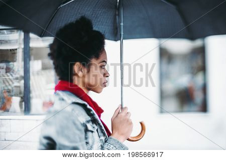 True tilt-shift portrait of afro american young cute girl holding an umbrella in rainy day on street in jean jacket and with red neckerchief blurred facade in background