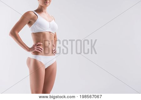 Close up of body of young slim jolly woman standing straight in white underclothes. She is keeping hands on hips. Copy space in right side. Isolated