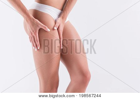 Close up of legs and hips of young sporty girl in panties. She is standing and touching her thigh muscle. Isolated