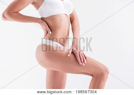 Close up of body of young slim woman standing in comfortable lingerie. Isolated
