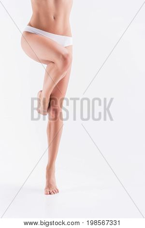 Close up of legs and belly of youthful slim lady in cotton panties standing on toes bending one leg. Focus on tummy. Isolated