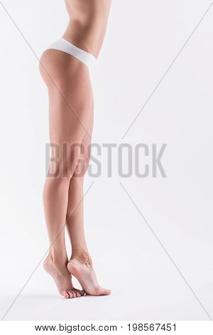 Close up of sporty youthful lady standing on toes cross-legged. She is wearing panties. Focus on body side