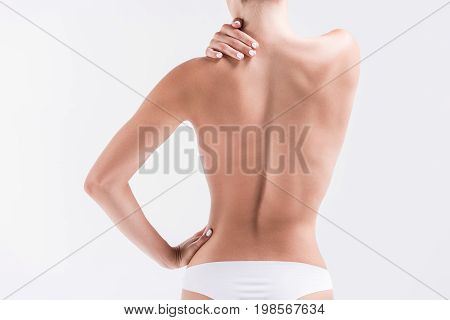Close up of body of young slim woman standing in panties touching her shoulder by hand. Isolated. Focus on back