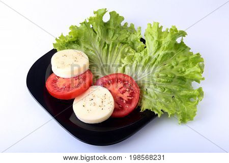 Portion of Mozzarella with Tomatoes, lettuce leaf and Balsamic dressing on black plate. selective focus close-up shot