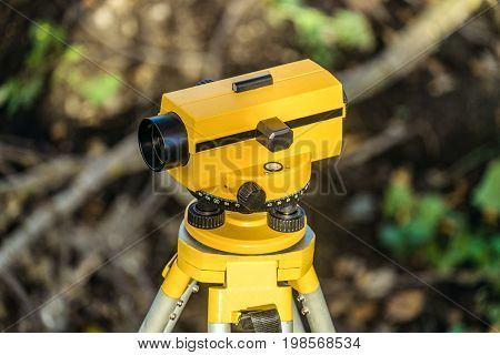 Yellow geodetic optical level on a tripod. Construction engineering equipment.