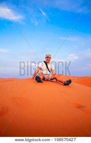 Tourist resting on top of the stunning sand dunes of Sahara desert in Merzouga, Morocco