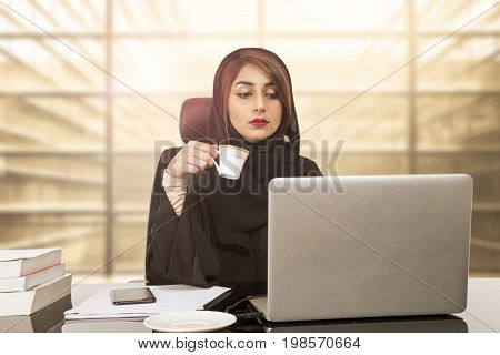 Arab Young business woman sitting at her desk in an office working on a laptop computer and drinking coffee or tea.