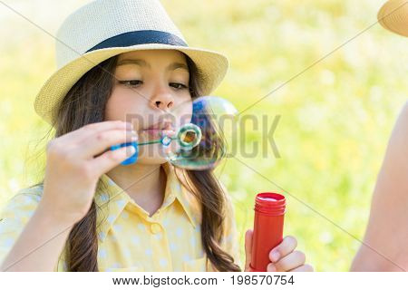 Portrait of concentrated pretty girl looking at large soap bubble while blowing it through the plastic circle. She is sitting on meadow near her mother