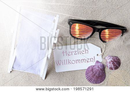 Sunny Summer Label With German Text Herzlich Willkommen Means Welcome. Flat Lay View. Summer Decoration With Deck Chair, Seashells And Sunglasses. Greeting Crad With Sand Background