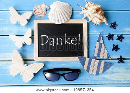 Flat Lay Of Chalkboard On Blue Wooden Background. Nautical Summer Decoration As Holiday Greeting Card. German Text Danke Means Thank You