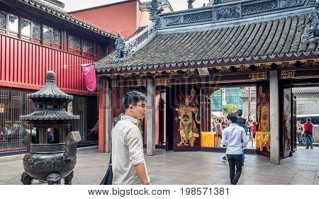 Shanghai, China - Nov 6, 2016: Gate to the 600-year-old Old City God Temple. Paintings of the City Gods on gate doors, and an incense urn in the courtyard. Visitors enter and exit through this gate.