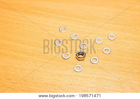 Heart made of metal washers with a nut on a wooden background small and durable tools for attaching