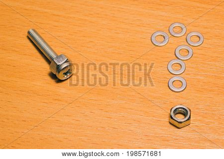 Metal screw with thread and screwed nut and question mark laid out of washers against a wooden background