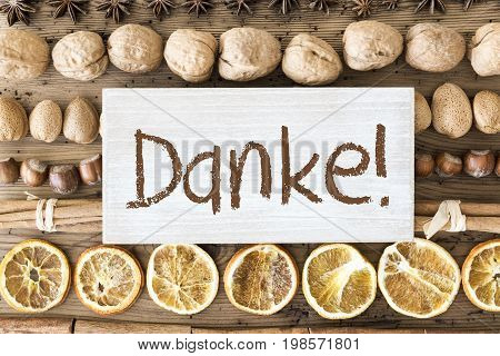 Sign With German Text Danke Means Thank You. Christmas Food Flat Lay With Walnut, Hazelnut, Cinnamon Sticks And Orange Peel. Brown Wooden Background