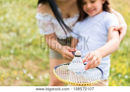 Excited child is holding tennis racket and putting shuttlecock on net with interest. Her mother is embracing her while standing on meadow. Girl is smiling. Focus on equipment