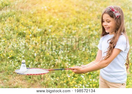 Cheerful little girl is playing tennis on meadow. She is holding racket and looking at shuttlecock with concentration. Kid is standing and laughing