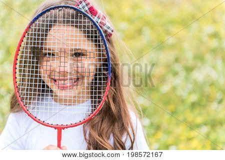 Portrait of joyful girl having fun on meadow while playing badminton. She is holding racket net in front of the face and showing tongue to camera. Child is laughing. Copy space in right side