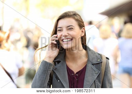 Teen laughing while talking on the phone on the street