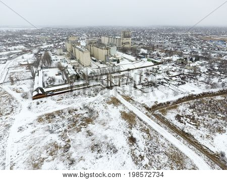 Sprinkled With Snow Grain Elevator. Winter View Of The Old Soviet Elevator. Winter View From The Bir