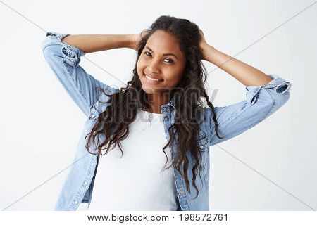 Studio shot of good-looking attractive young Afro-American woman in denim shirt and white t-shirt playing with her long wavy hair, smiling broadly with her perfect white teeth to the camera. Dark-skinned cheerful female posing on white background.