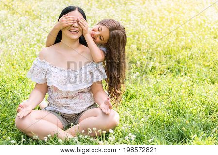 Guess who it is. Cheerful girl is covering eyes of her mother secretly. Woman is sitting in lotus position on grass during meditation and laughing. Copy space