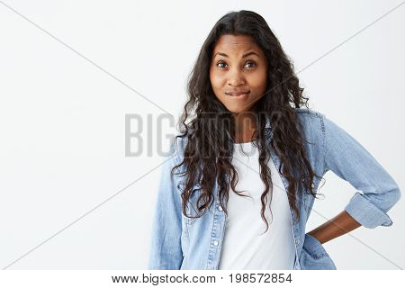 Discontent Afro-american female with loose wavy hair curving her lips, having grumpy expression being dissatisfied with something. Young female student with unsatisfied expression.