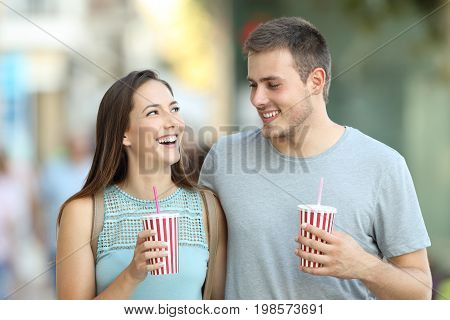 Front view portrait of a happy couple talking and holding takeaway refreshments in the street