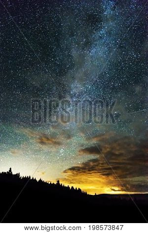 Milky Way And Sky Full Of Stars Reaching Across The Night Sky, Light From Horizon Behind Treed Mount