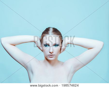 Attractive blonde naked woman with dark eye make up.