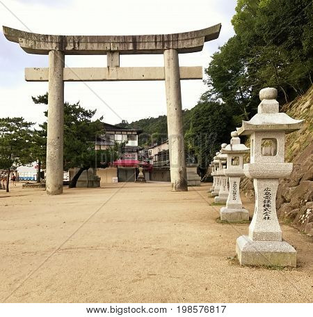 Stone Tori gate at the entrance to the sacred grounds of the Itsukushima Shrine and Floating Torii Gate.