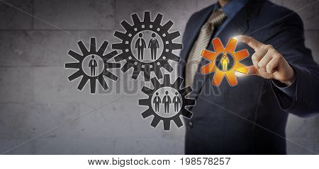 Blue chip manager is adding a cog encircling a female employee to a gear train of white collar workers. Business concept for team building teamwork gender equality choosing the right person.