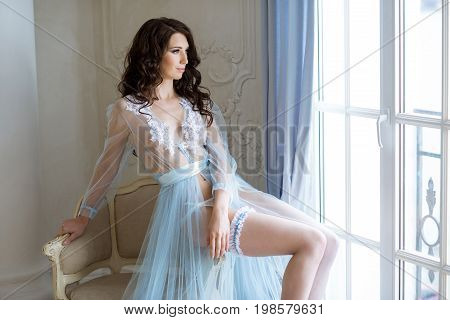 Beautiful sexy lady in elegant blue robe. Close up fashion portrait of model indoors. Beauty brunette woman in garter. Attractive female body in lace lingerie. Closeup naked girl in underwear