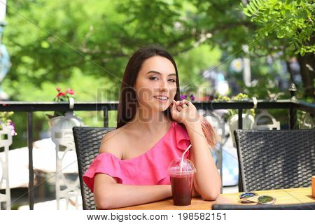Lively young woman drinking fresh smoothie in cafe