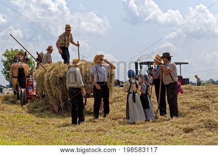 NEW HOLLAND PENNSYLVANIA - August 4 2017: Two young Mennonite girls take water to the hay crew at Big Spring Farm Days. This is an annual event demonstrating traditional threshing and harvesting methods using restored antique and vintage tools.