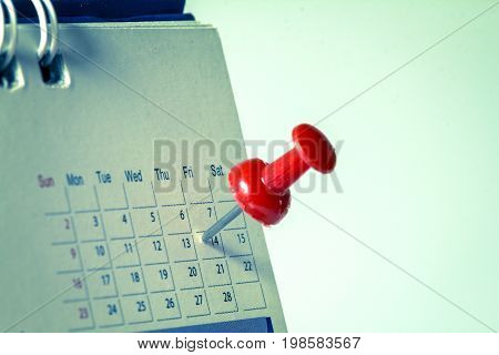 Red pushpin on calendar page for remind and marked important events vintage retro color tone
