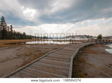 Boardwalk next to Tangled Creek and Black Warrior Springs leading into Hot Lake in the Lower Geyser Basin in Yellowstone National Park in Wyoming United States