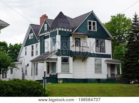 CADILLAC, MICHIGAN / UNITED STATES -  MAY 31, 2017: An historic green and white mansion with a corner turret in Cadillac's Courthouse Hill Historic District.