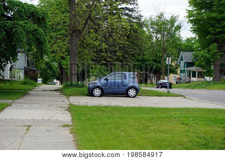 CADILLAC, MICHIGAN / UNITED STATES -  MAY 31, 2017: A small blue Toyota Scion is parked in a driveway in Cadillac's Courthouse Hill Historic District.