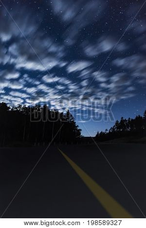 Night Scene With Dark Road, Highlighted Center Yellow Line, Beneath A Majestic Sky Full Of Stars And