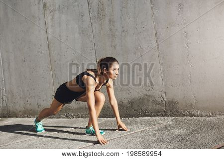 Female athlete ready to start running in concrete jungle. Urban sport concept.