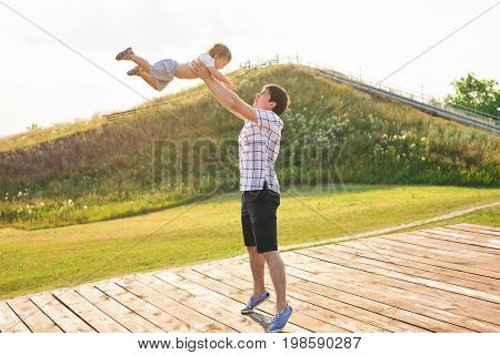 Happy young father and son playing together and having fun in the summer or autumn field. Family, child, fatherhood and nature concept.