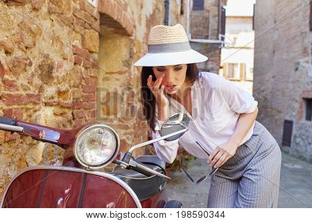 Woman looking at herself in scooter mirror