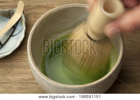 Preparing a bowl of matcha tea with a tea whisk