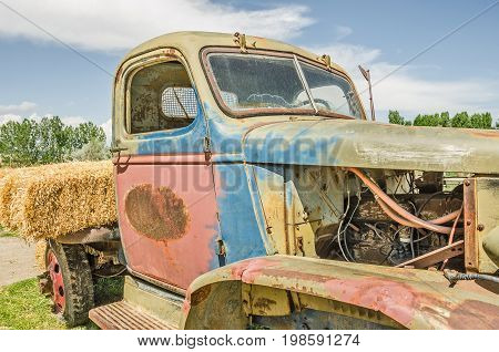 Close-up of old colorful vintage truck missing some parts and rusting in places