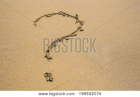 question mark drawn on the sand of a beach