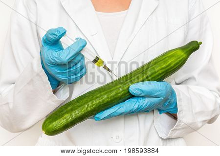 Gmo Scientist Injecting Liquid From Syringe Into Cucumber