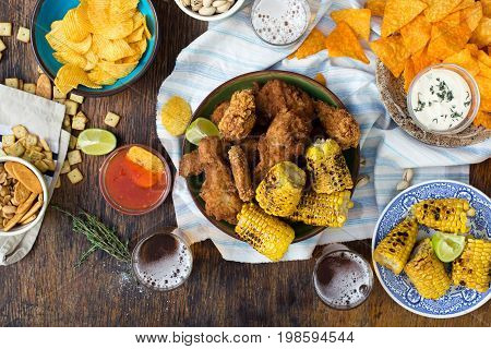Fried chicken beer and snacks to beer on wooden table top view. Party dinner table concept.